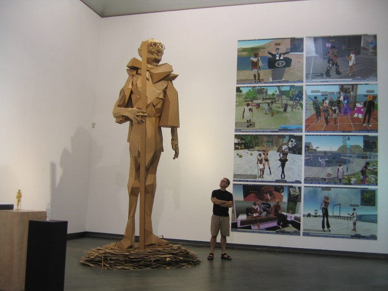 Joseph DeLappe standing next to a large sculpture of his Gandhi avatar