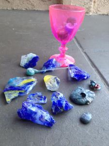 pink goblet and small pieces of blue and yellow glass on a large grey slab