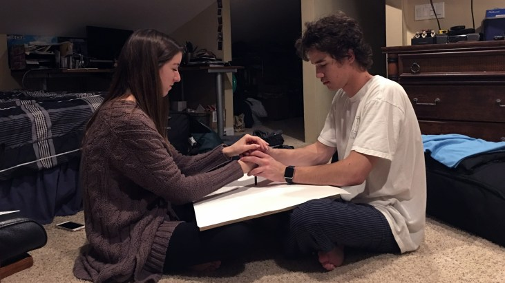 Elizabeth Moledo and her boyfriend Aaron making an Automatic Drawing by facing each other, holding their hands on a pencil over a sheet of drawing paper between them, and letting the pencil go where it will