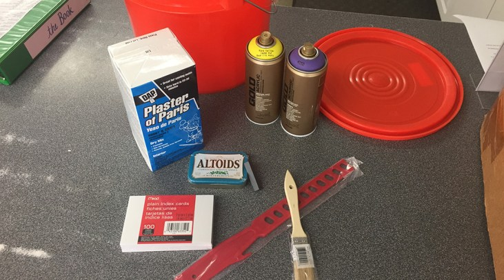 photo of the contents of the Art 110 Art Kit: Bucket, plaster, stir stick, paint brush,  2 cans of Montana Gold paint, package of 100 unlined index cards, tin of Altoids mints and a bar magnet