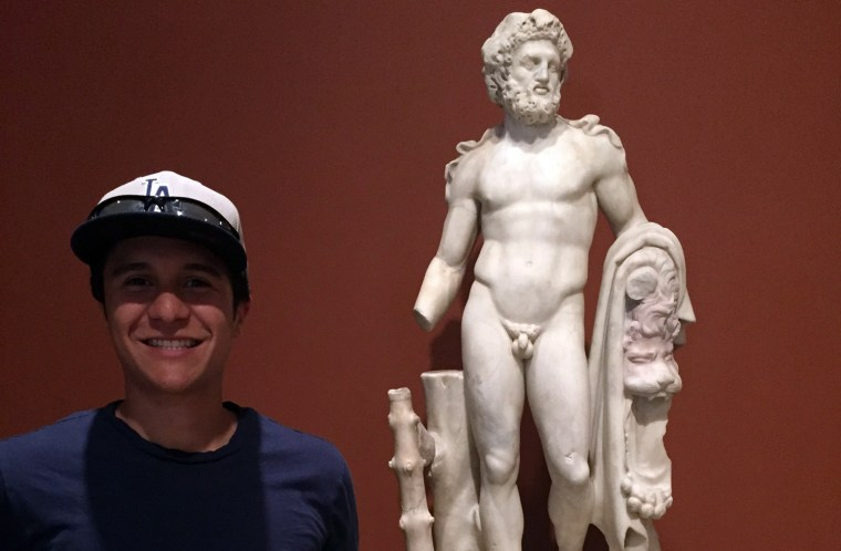 Drew Sanchez standing in front of a statue at the Getty Villa