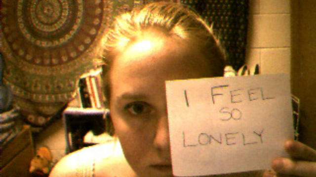 "screencap of Jennifer Ringley looking at her webcam and holding up a note that reads ""I feel so lonely"""