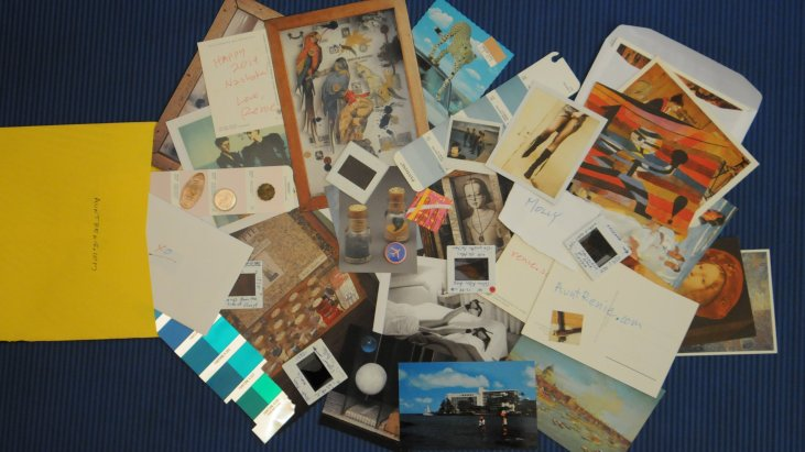 "an ""Art Care Package"" - a large envelope filled with many bits of ephemera: photographs, slides, paint chips, audio CD's, foreign coins, and other materials"