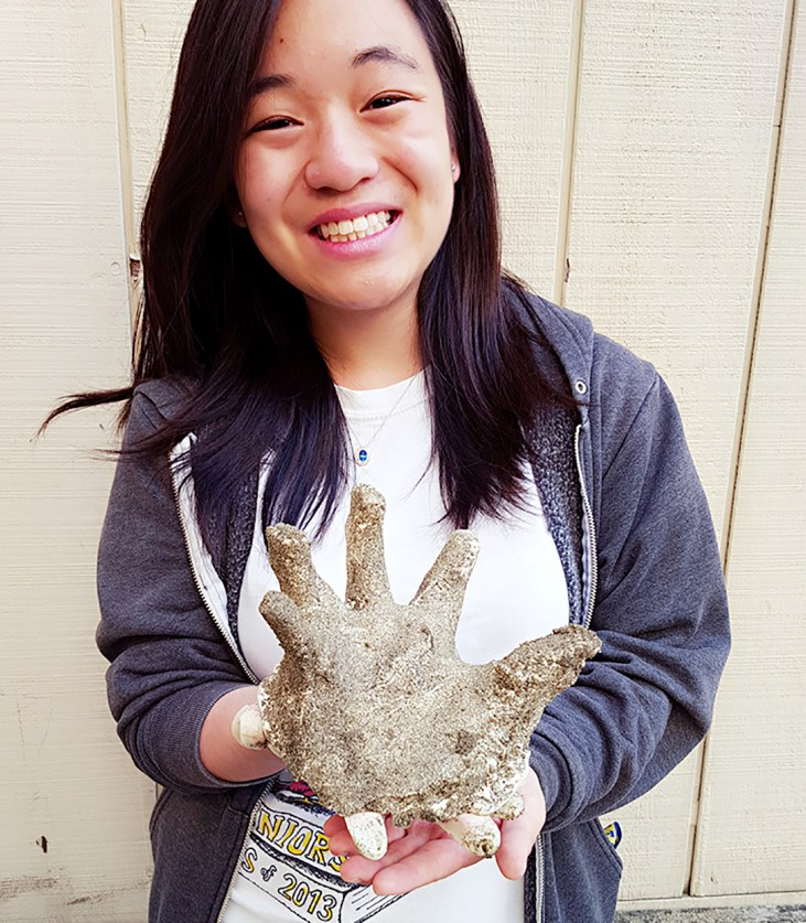 Elizabeth Chen holding a plaster casting of her hand