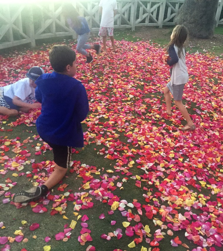 kids with a zillion rose petals on the grass