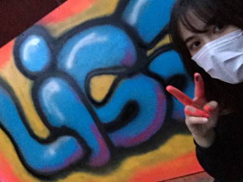 "Lisa Bernhauser wearing a filter mask and making a peace sign in front of a graffiti writing piece of her name ""Lisa"""