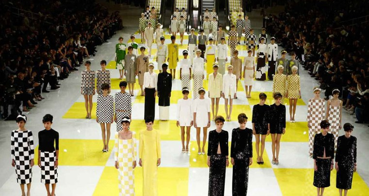 Many models in Marc Jacobs / Louis Vuitton white-black-yellow pattern clothing set against a floor and escalator system by Daniel Buren