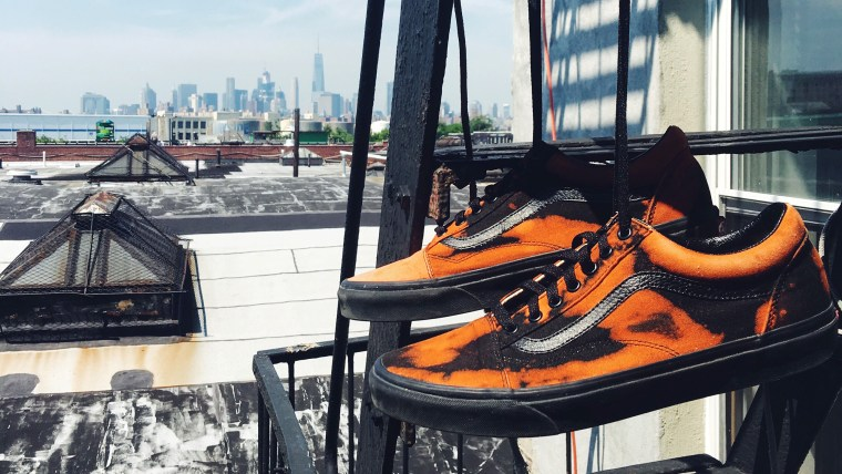 A pair of black and orange tennis shoes hanging from the fire escape outside an apartment building in New York City with towers and other buildings in the distance