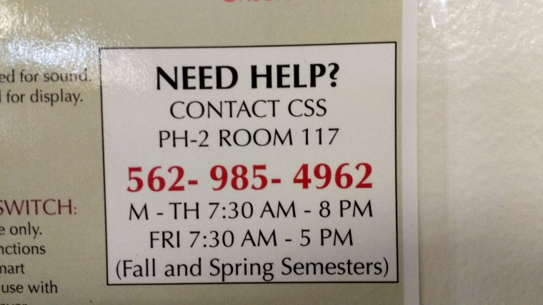 """photo of a """"need help?"""" sign next to the projection """"smart panel"""" in classroom FA4-311 in the School of Art at CSULB"""