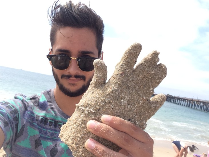 Adrian Munoz holding a plaster casting of his hand