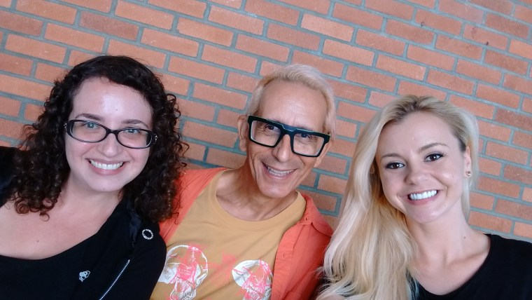 Photo of Rhiannon Aarons, Glenn Zucman & Bree Olson sitting and smiling in front of a red brick building on the CSULB campus
