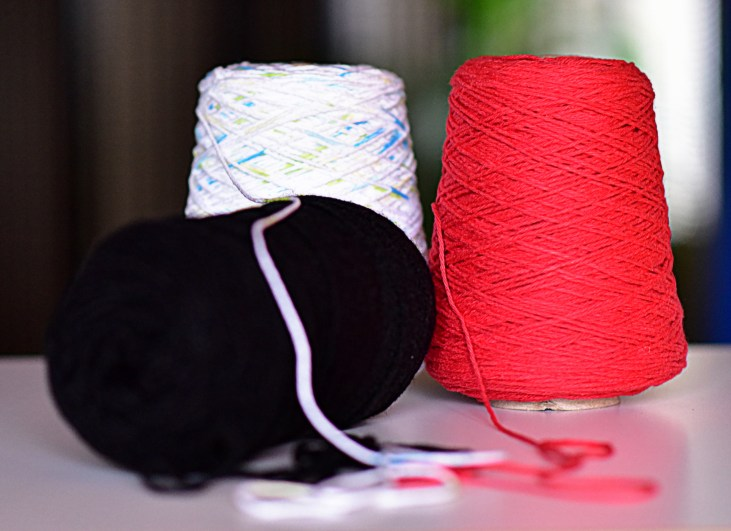 Photo of 3 spools of yarn: Black, Red & White