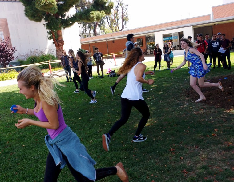 """Students running to collect works of art at an outdoor """"art auction"""""""