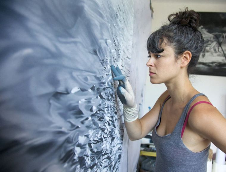 Zaria Forman in front of a painting in progress