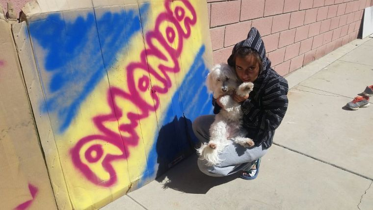 """Amanda Martinez and her dog Tofu in front of the name """"Amanda"""" painted in bubble letters on a large sheet of cardboard"""