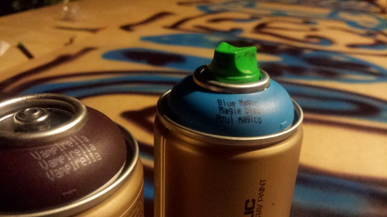 """two cans of Montana Gold spray paint, in the colors""""Black Magic"""" and """"Vampirella"""""""