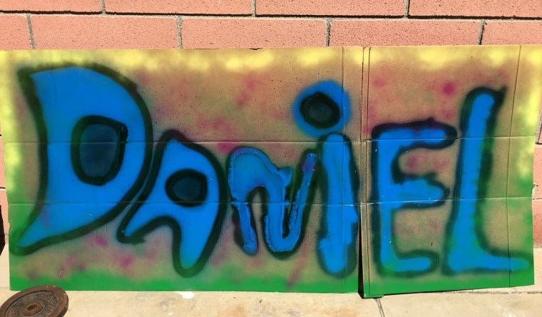 """the name """"Daniel"""" in blue spray paint with a black outline and against a background of yellow and green on a large sheet of cardboard"""