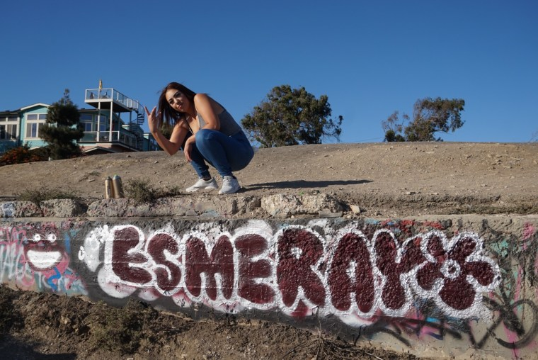 Esmeray Lopez standing over a low wall where her name is painted in bubble letters at Sunken City in San Pedro, CA