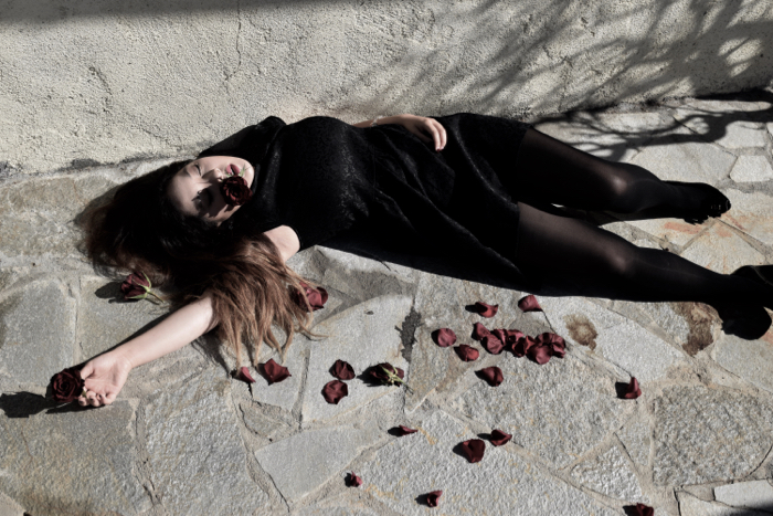 """simulated """"death by heartbreak"""" - a body on the ground surrounded by rose petals"""