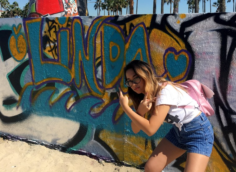 Linda-Linh Nguyen in front of her name on a wall at the Venice Beach, CA Art Walls