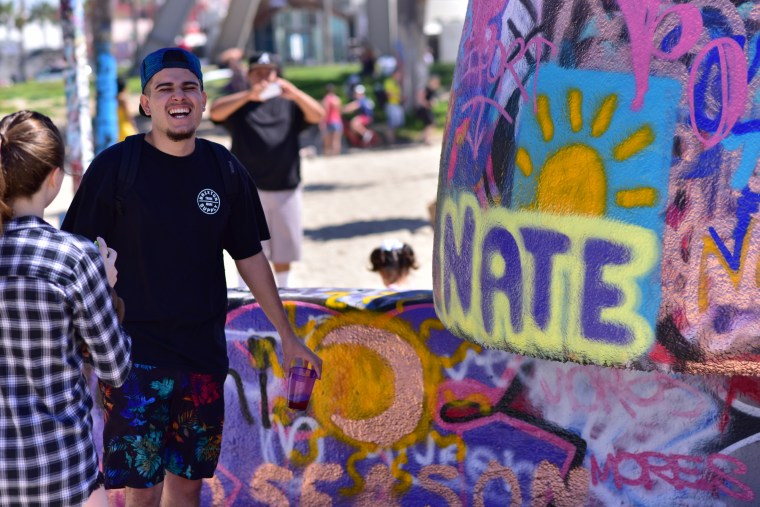 "Nathan Davalos in front of ""Nate"" painted in yellow and purple on the Venice Art Walls"