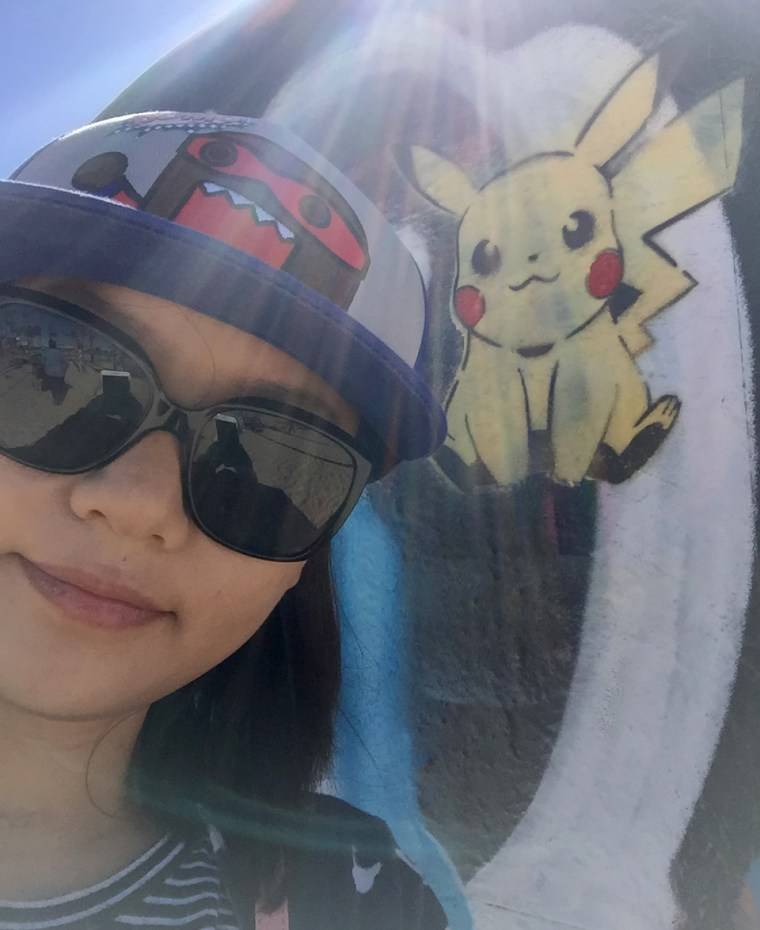 Ruiwen Lin in front of a stencil painted Pikachu at the Venice Art Walls