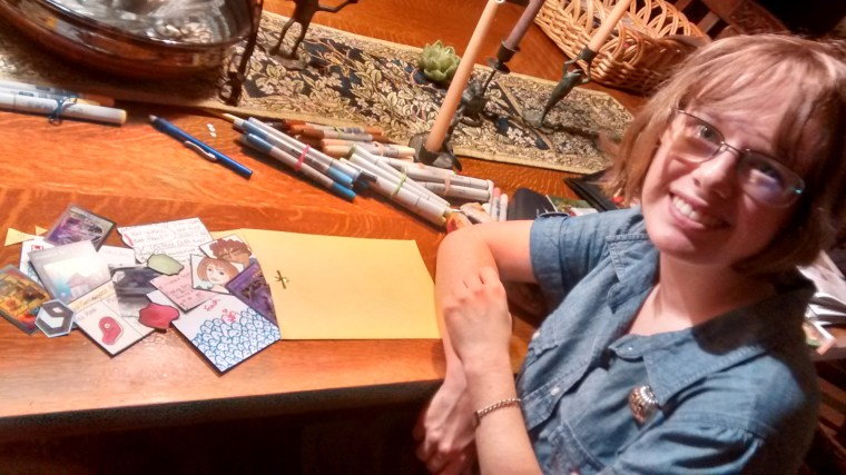 photo of Hannah Adams at her desk with an Art Care Package she has created. The package is a large envelope filled with many small illustrations by Hannah.