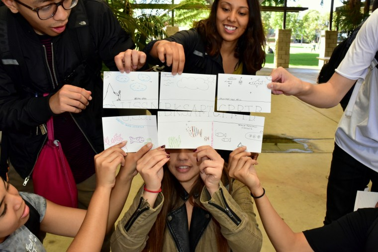 6 students holding 4x6 index cards to make up one large drawing