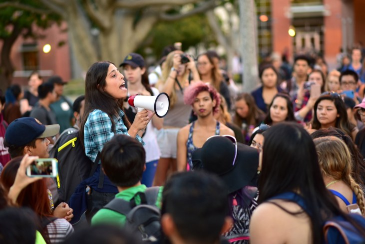 a student with a megaphone speaking to a crowd of fellow students