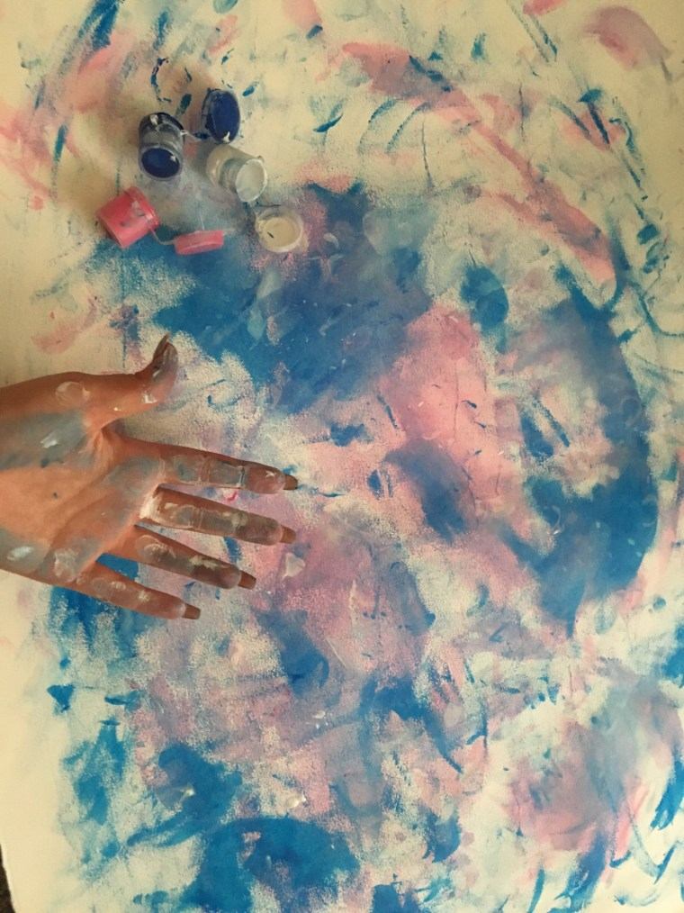acrylic finger painting on paper in red, blue, and white, and with Esmeray Lopez' paint-covered hand held over the photo of the painting