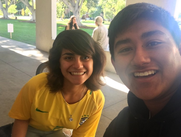 Fatima Negrete in a yellow Nike soccer jersey, and Alfredo Reyes in a black hoodie, smiling in the CSULB School of Art, Art Gallery Courtyard