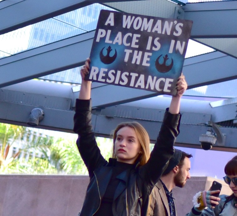 "A woman at the Los Angeles Women's March on 21 January 2017 holding a sign that reads ""A Woman's Place is in The Resistance"""