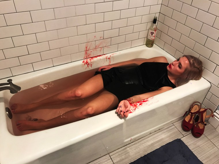 Jennifer in a LBD in a bathtub staging a photo of her death