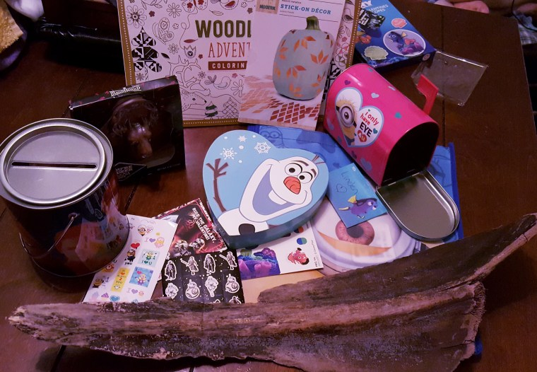 pieces of ephemera, chocolate, and a coloring book spread out on a wooden table