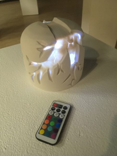 ceramic sculpture with a remote control to turn lights on inside of the sculpture