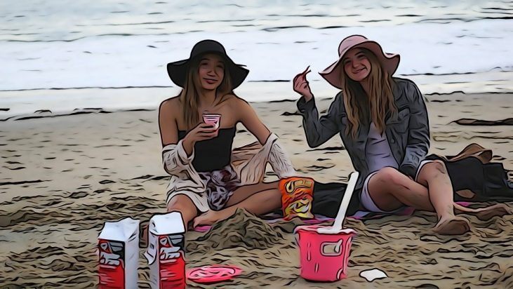 students sitting on the beach and enjoying a large bag of Flaming Hot Cheetos