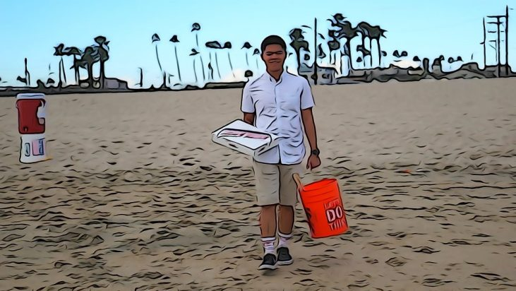 student carrying a box of Krispy Kreme donuts to the beach