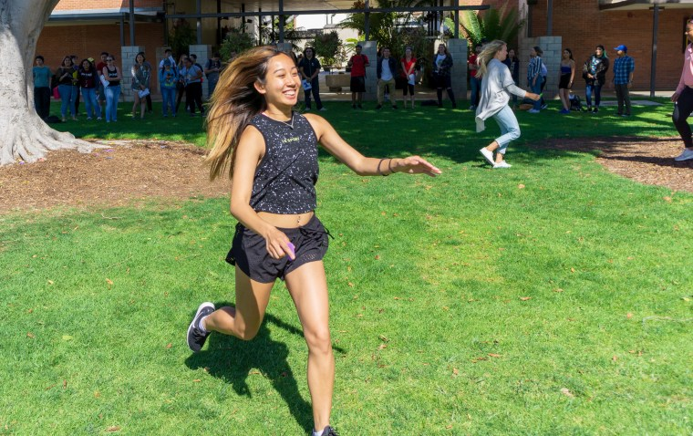 a student running with a foam letter representing a work of art