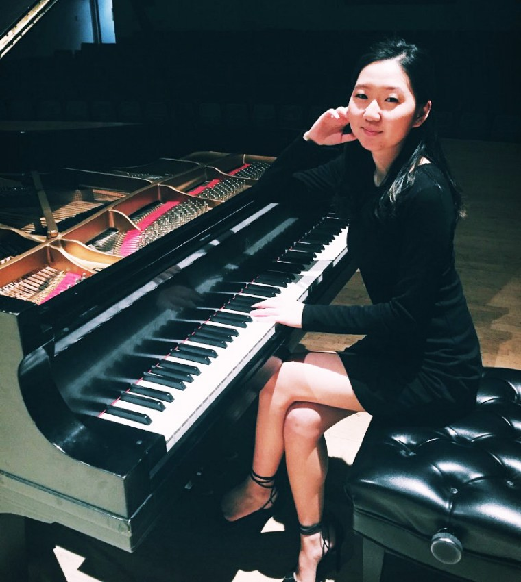 Yeunje Kim in a black dress and seated at a grand piano