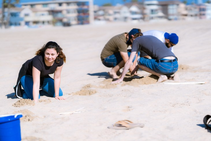 students creating plaster casting projects in the sand at the Seal Beach Pier