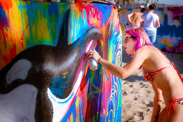 painter and street artist Lizzie Green spray painting a piece at the Venice Beach Art Walls. Green paints a whale in black and white, and surrounding the whale a brightly colored background field. Lizzie Green's own haircolor in fuschia and orange resonates with the colored spraypaint on the wall