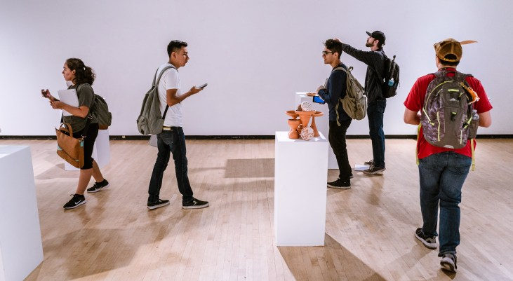 students in Long Beach State University's Gatov Gallery viewing an art installation