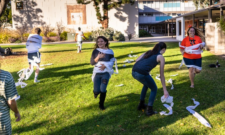 """students """"wrapped"""" as mummies (with toilet paper) running down the grass in the center of the Long Beach State University campus"""