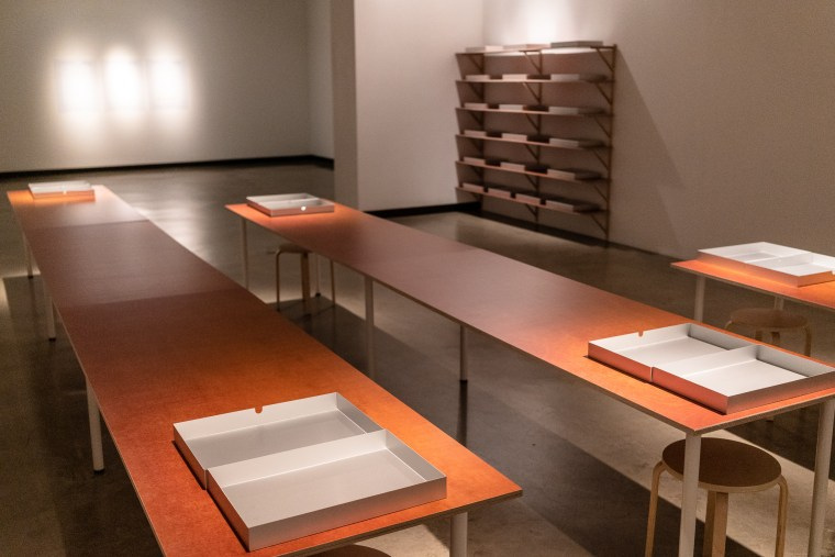 room view of 3 tables and shelves of aluminum boxes