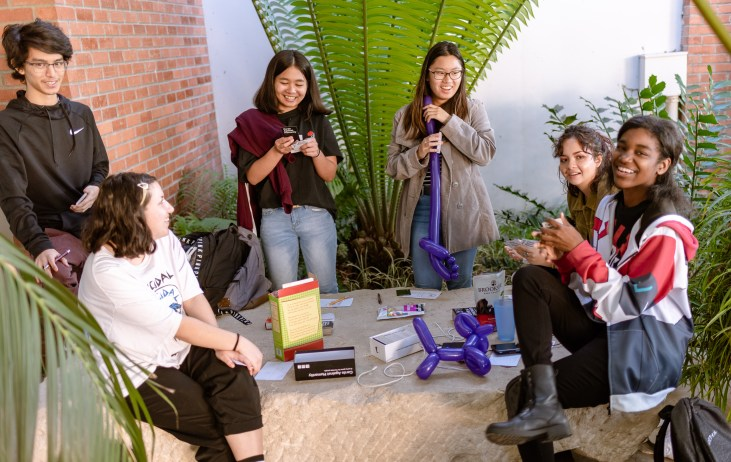 a group of 6 students sit on a large stone in the School of Art, Art Gallery Courtyard at Long Beach State University and play games and eat snacks.