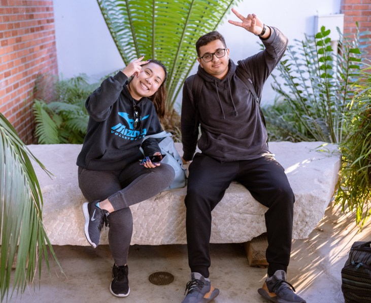 2 students sitting on a large stone in the Art Gallery Courtyard at Long Beach State University.