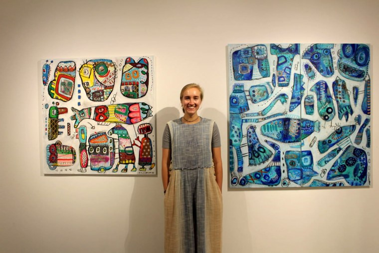 Agora Gallery intern  Anna Merritt, pictured with artworks by Eileen Olimb.