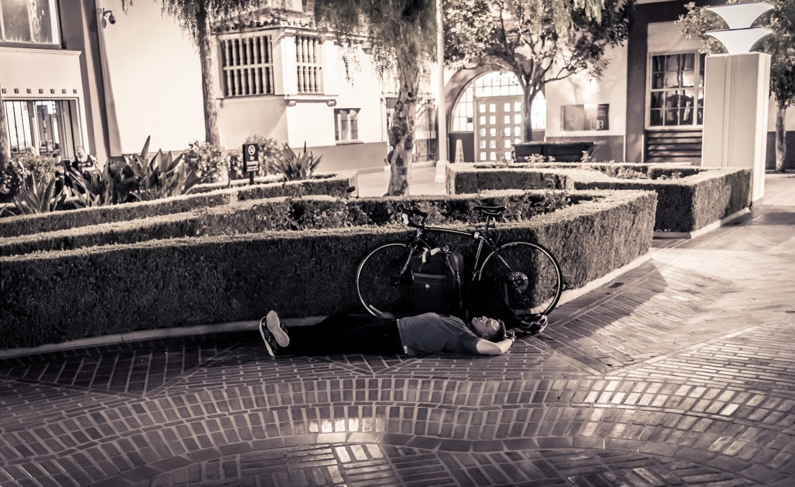 A guy laying down on the bricks in the Union Station courtyard. Parked next to him is a 10-speed bicycle.