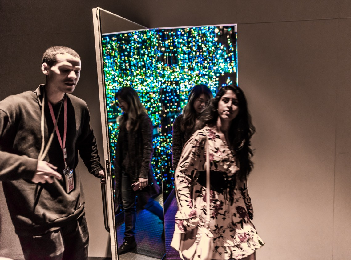 A visitor services associate holds a door open for people leaving one of Yayoi Kusama's infinity rooms