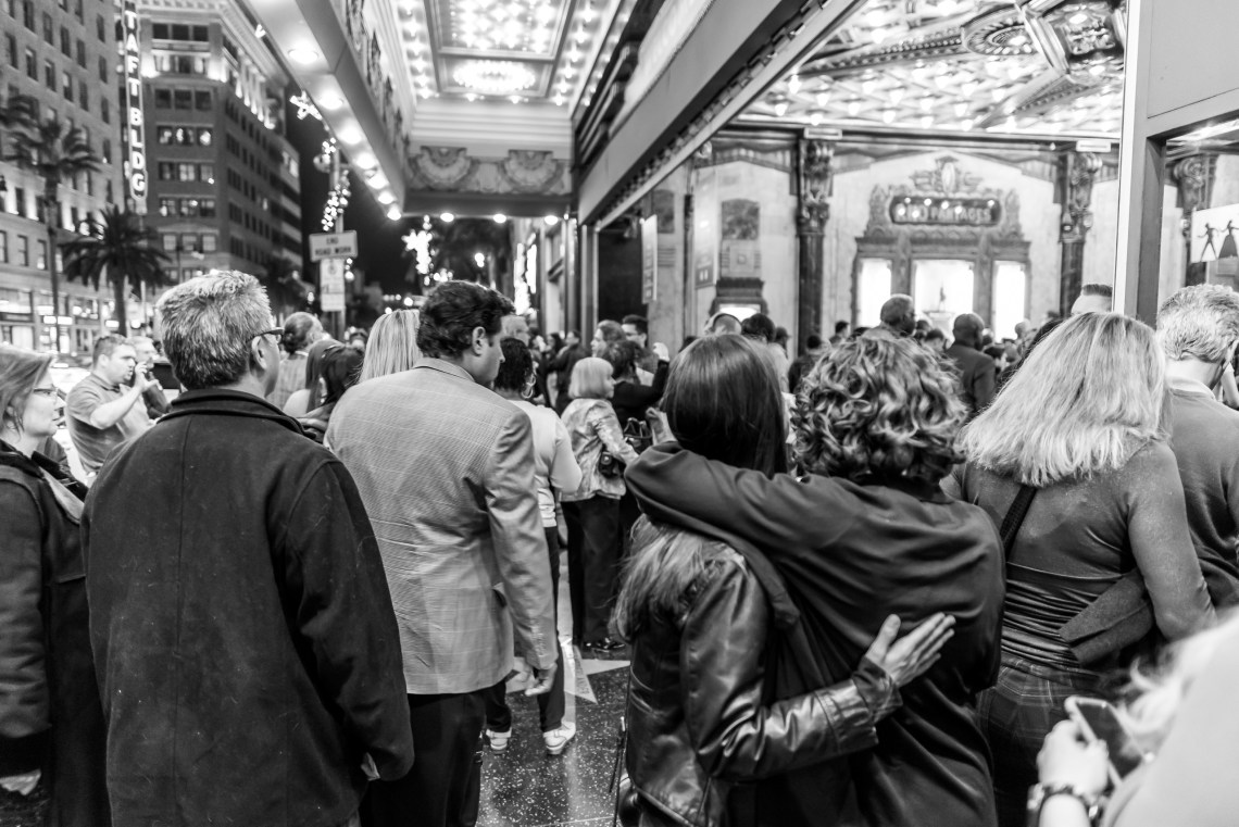 a crowd moves toward the theatre entrance, and two women share a hug as they walk in